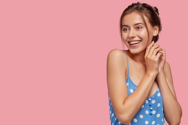 Довольно очаровательная молодая девушка с очаровательной улыбкой держит руки вместе Бесплатные Фотографии