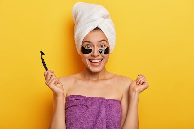 かなり陽気な女性は、純粋な肌を持ち、タオルに包まれて立って、かみそりの刃を持って、ひげそりの準備をし、衛生的な治療を受け、さわやかに見え、優しく微笑む 無料写真