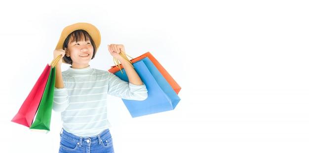 Милая девушка ребенка вручает держать хозяйственную сумку изолированный на белой предпосылке. Premium Фотографии
