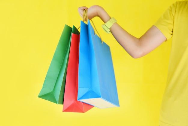 Милая девушка ребенка вручает держать хозяйственную сумку изолированный на желтой предпосылке. Premium Фотографии