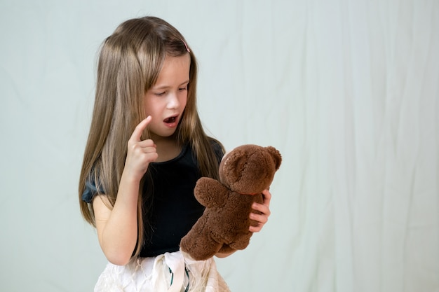 Pretty child girl playing with her teddy bear toy. Premium Photo