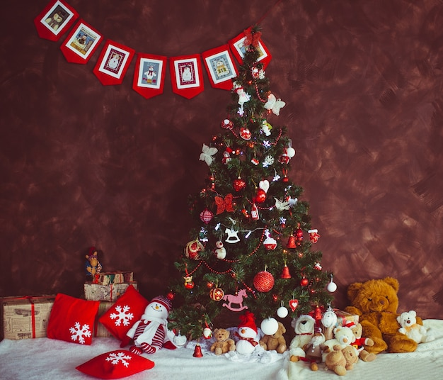 Pretty christmas tree stands before a red wall Free Photo