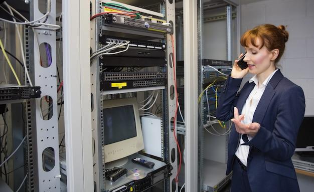 Pretty computer technician talking on phone beside open server Premium Photo