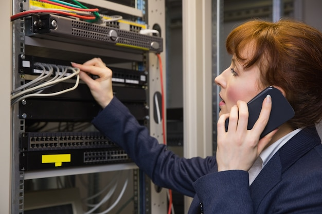 Pretty computer technician talking on phone while fixing server Premium Photo
