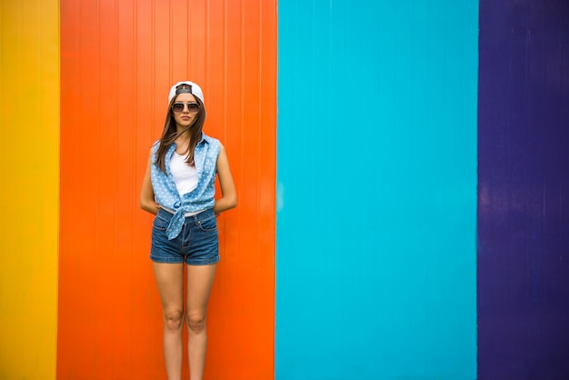 Pretty cool girl in sunglasses and cap standing against. Premium Photo