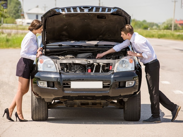 Pretty couple is trying to repair their car using manual. Premium Photo