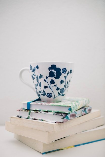 Pretty cup on pile of books Free Photo