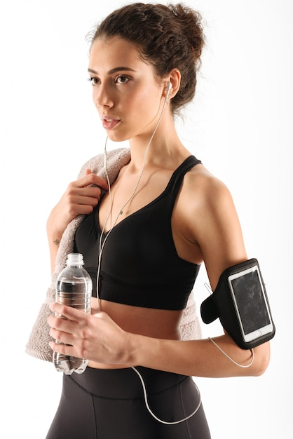 Pretty curly brunette fitness woman with bottle Free Photo