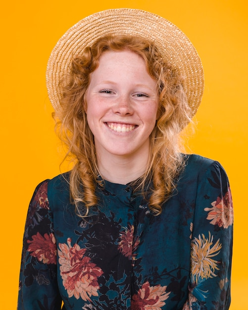 Pretty curly redheaded female in studio with bright background Free Photo