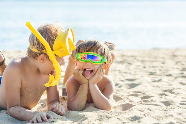 Pretty cute children on the beach having fun. smiling kids in the summer time. boys outdoors. Premium Photo