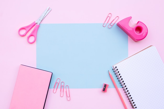 Pretty desktop composition with notebook, scissors, and books on pink background with blu Free Photo