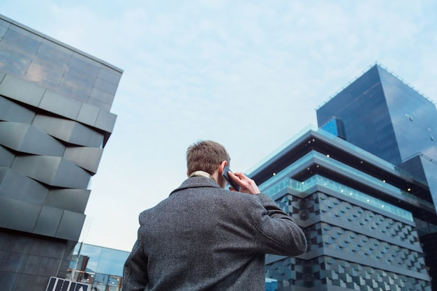 A pretty dressed man talking on a mobile phone in front of an office skyscraper Premium Photo