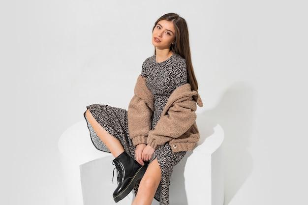 겨울 모피 코트와 세련된 드레스 앉아 예쁜 유럽 여자. 블랙 가죽 소재의 앵클 부츠를 신고 있습니다. 무료 사진