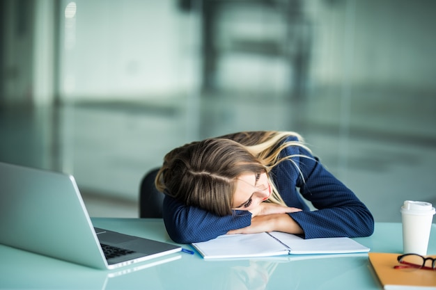 Pretty exhausted young businesswoman sitting at her desk sleeping in her office Free Photo