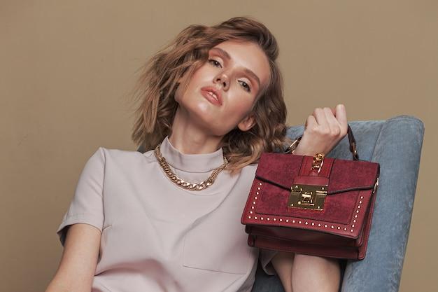 Портрет девушки довольно светлых волос с кожаным рюкзаком цвета меди. Premium Фотографии