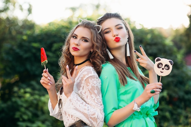 Pretty and fashionable girlfriends holding candies on stick. Premium Photo