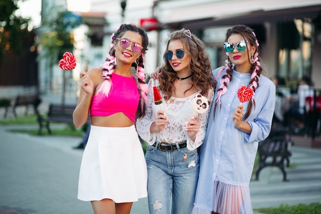 Pretty and fashionable girls holding candies heart on stick. Premium Photo