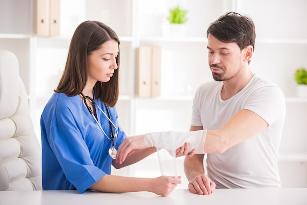 Pretty female doctor is bandaging upper limb of young man. Premium Photo