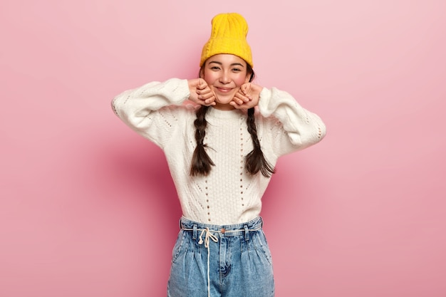 Pretty female dressed in fashionable yellow hat, white sweater and jeans, has enthusiastic and charming look in camera, glad expression, isolated over pink wall Free Photo