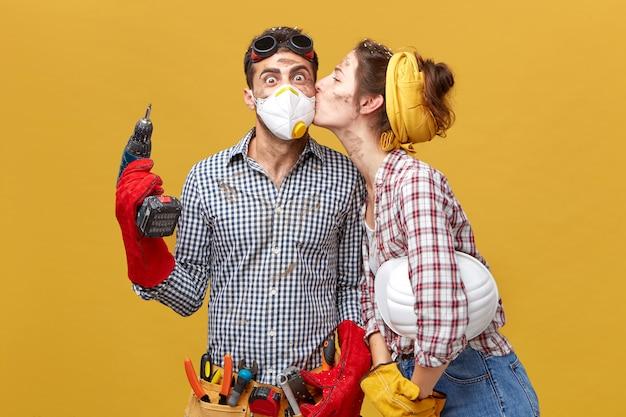 きれいな女性が彼女のワードローブを修理してくれたことに感謝している頬に夫のキスをしている。彼のガールフレンドからのキスを受け取って喜んでいる掘削機を保持しているマスクで驚いた男性労働者 無料写真