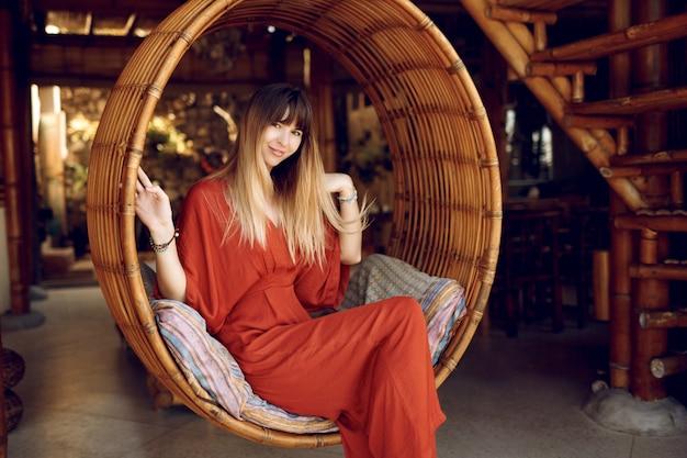 Ubicazione femminile graziosa nell'attaccatura della scala di bambù sulla veranda all'aperto del bungalow di legno Foto Gratuite