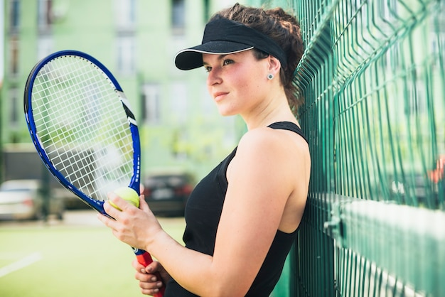 Pretty female tennis player holding a racket outdoors Free Photo