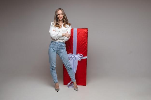 휴일 광고 복사 공간이 회색 스튜디오 배경에 큰 빨간 선물로 꽤 맞는 젊은 여자 무료 사진