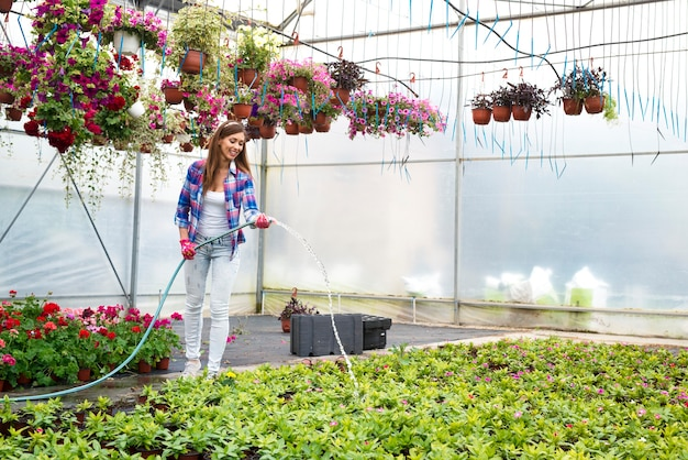 Pretty florist woman with hose watering potted flowers in plant nursery greenhouse and keeping them alive and fresh for sale Free Photo