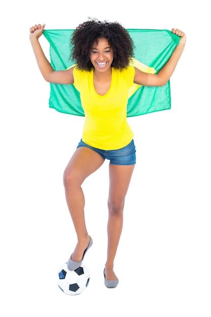 Pretty football fan holding brazilian flag cheering at camera Premium Photo