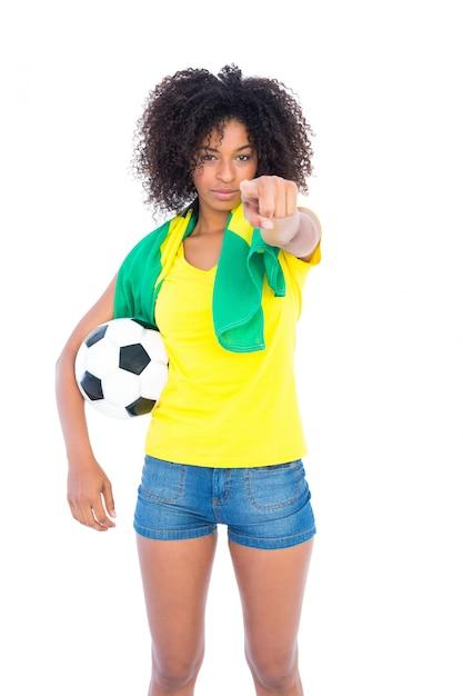 Pretty football fan holding brazilian flag pointing at camera Premium Photo