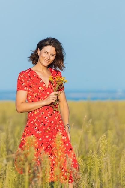 緑の野原で野外を歩いていると黄色の花の花束を持ってかなり夏の赤いドレスを着ているかなり新鮮な若い女性。村での夏休みのコンセプトとライブスタイル Premium写真