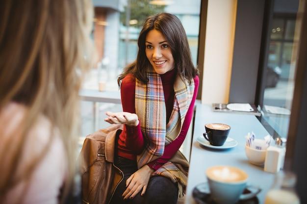 Pretty friends chatting over coffee in cafe Premium Photo