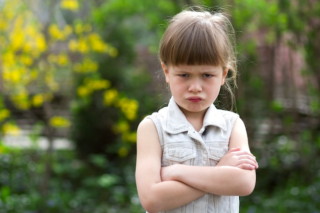 Pretty funny moody little blond preschool girl in white sleeveless dress looks into camera feeling angry and unsatisfied on blurred summer background. Premium Photo