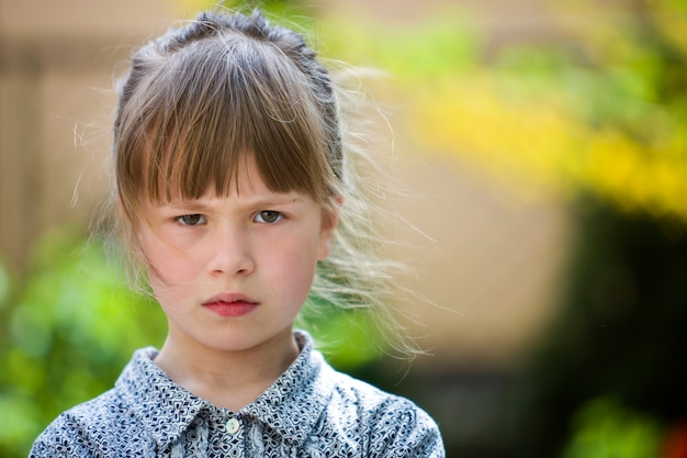 Pretty funny moody young child girl outdoor feeling angry and unsatisfied on blurred summer green . children tantrum . Premium Photo