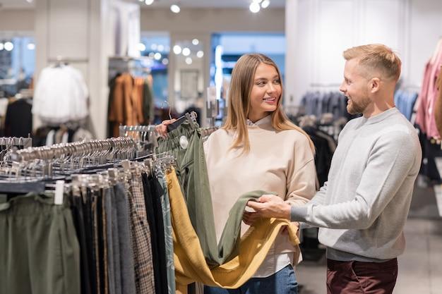 きれいな女の子と若い男がモールでの販売中に新しいパンツのペアを購入しようとしているときに黄色と灰色の色の間で選択 Premium写真