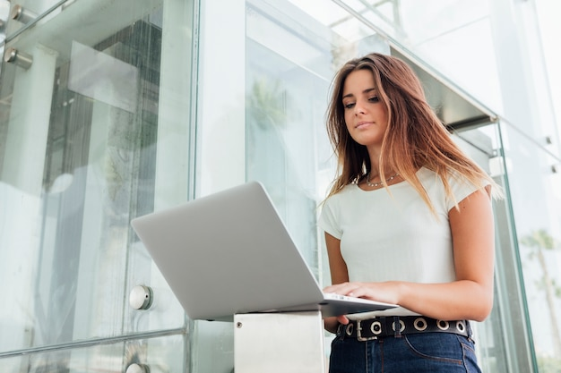 Pretty girl browsing the internet on a laptop Free Photo