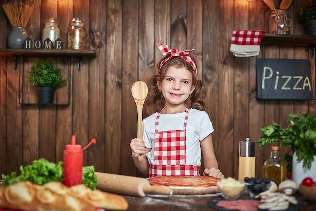 Pretty girl in checkered apron cooking pizza Premium Photo