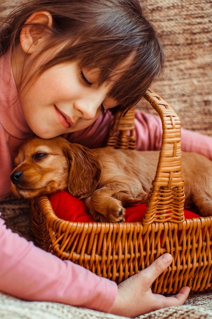 The pretty girl embarcing a basket with dog Free Photo