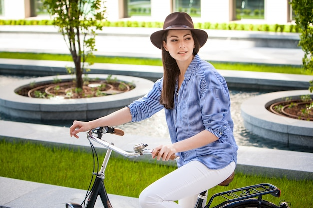 Pretty girl in hat riding a bicycle at street Free Photo