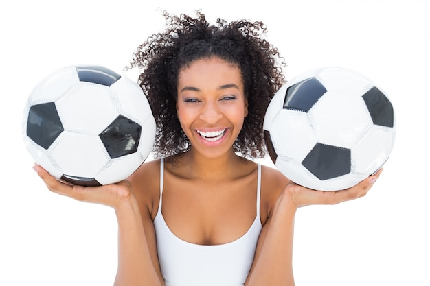 Pretty girl holding footballs and laughing at camera Premium Photo