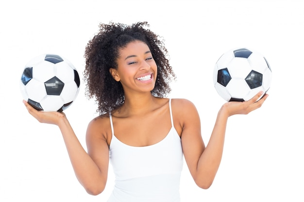 Pretty girl holding footballs and smiling at camera Premium Photo