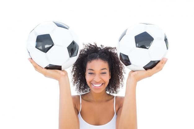 Pretty girl holding footballs and smiling at camera Premium Photo
