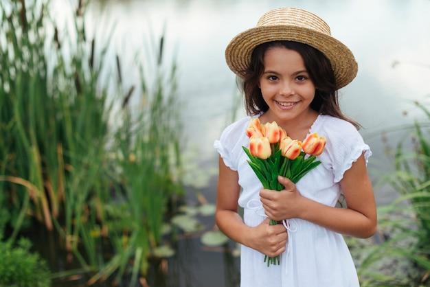 Pretty girl holding tulips medium shot Free Photo