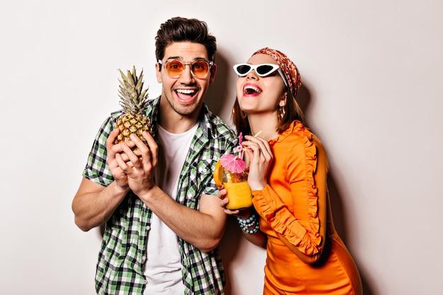 Красивая девушка в оранжевом платье и парень в зеленой рубашке и солнечных очках смеются и позируют с ананасом и коктейлем. Бесплатные Фотографии