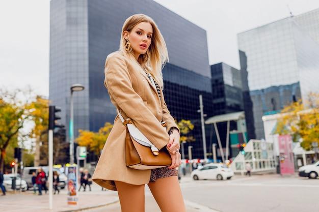 春のカジュアルな服装でかわいい女の子が屋外を歩いて、大きな近代的な都市で休日を楽しんでいます。ウールベージュのコートと剥奪されたブラウスを着ています。スタイリッシュなアクセサリー。 無料写真