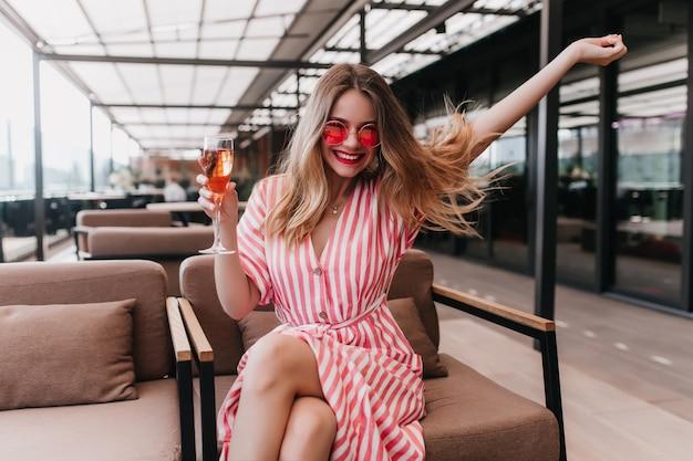 여름 날에 긍정적 인 감정을 표현하는 스트라이프 드레스에 예쁜 여자. 멋진 여성 모델의 실내 사진은 샴페인 잔을 들고 분홍색 선글라스를 착용합니다. 무료 사진