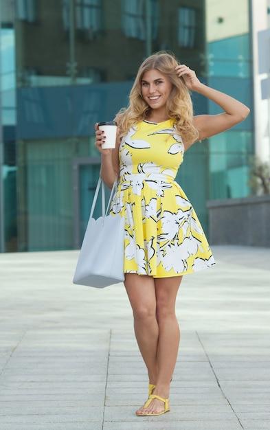 Красивая девушка в летнем платье на улице с утренним кофе Premium Фотографии