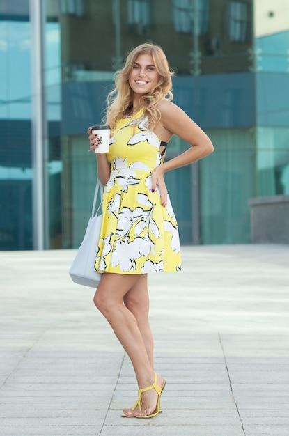 朝のコーヒーと路上で夏のドレスのかわいい女の子 Premium写真