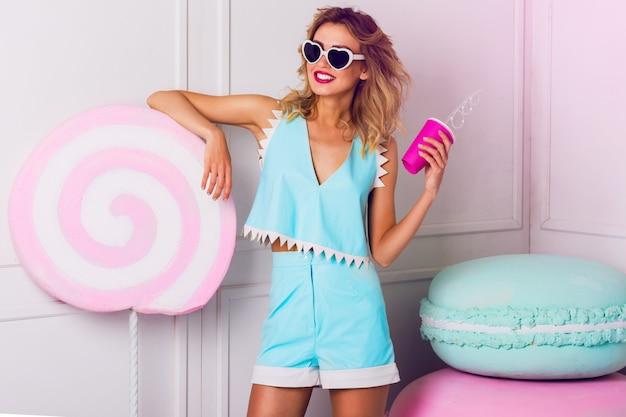 Красивая девушка в солнцезащитные очки с красивой кожей и губами, позирует в студии, пить фруктовый сок или коктейль. носить винтажные солнцезащитные очки с сердцем, стильный синий кожаный топ. Бесплатные Фотографии