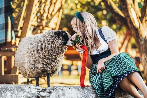 ファームのかわいい羊のそばに座って花の花束と伝統的なオクトーバーフェストドレスでかわいい女の子 Premium写真